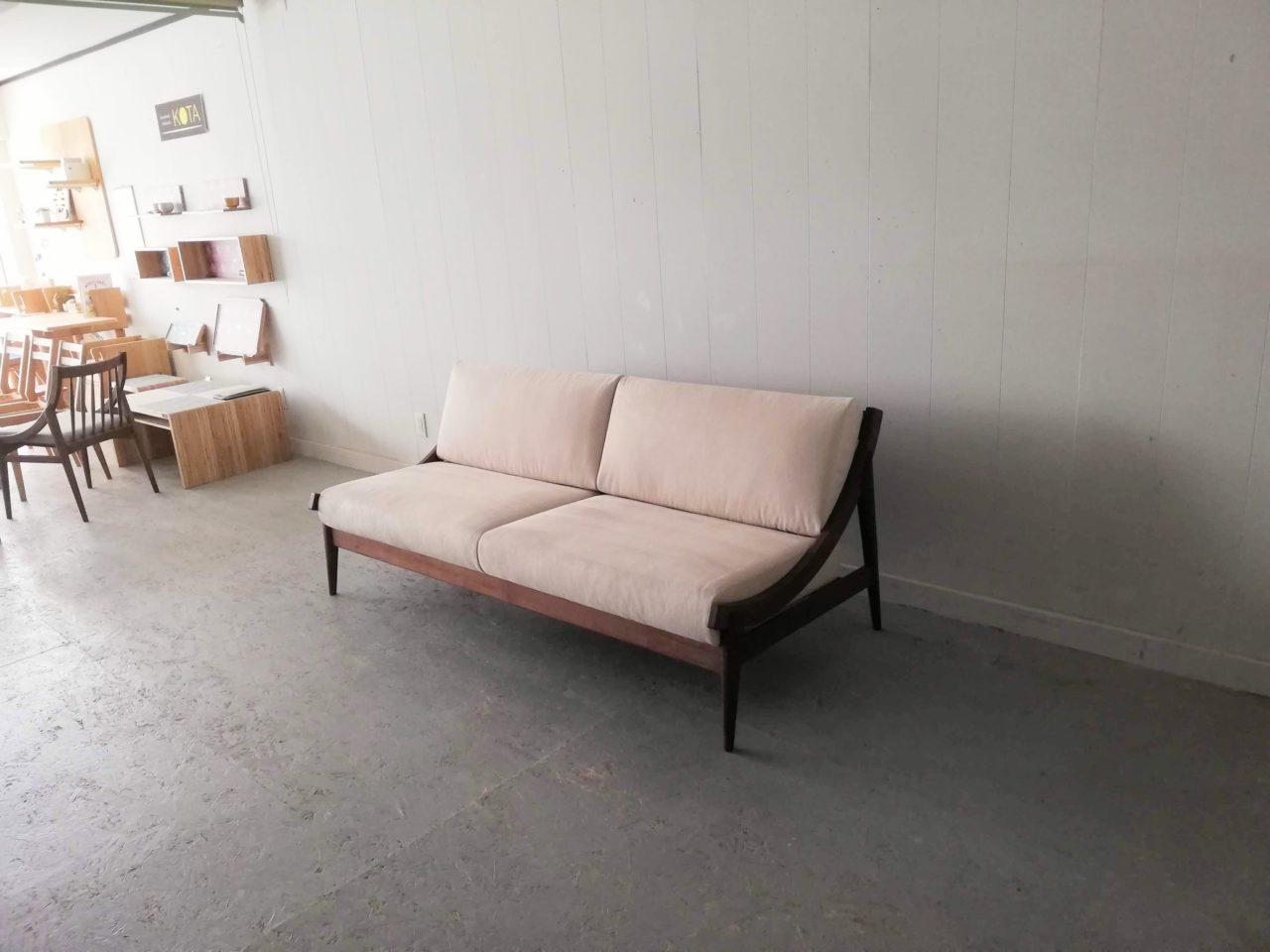 アームレスのソファーです。 両サイドの特徴のあるRの木部は、上がると肘付きに、下がると肘無しと呼べるタイプとなります。